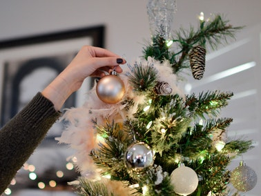 person reaching up to decorate tallest part of Christmas tree...