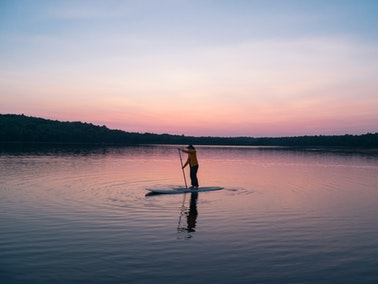 person on a paddleboard in the evening