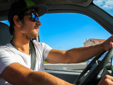 Man wearing sunglasses and hat driving in summer