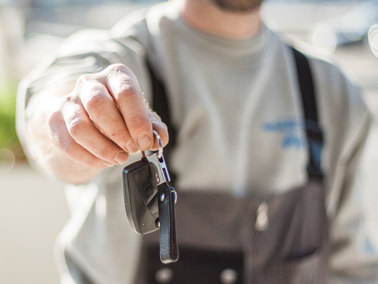 man holding out car keys