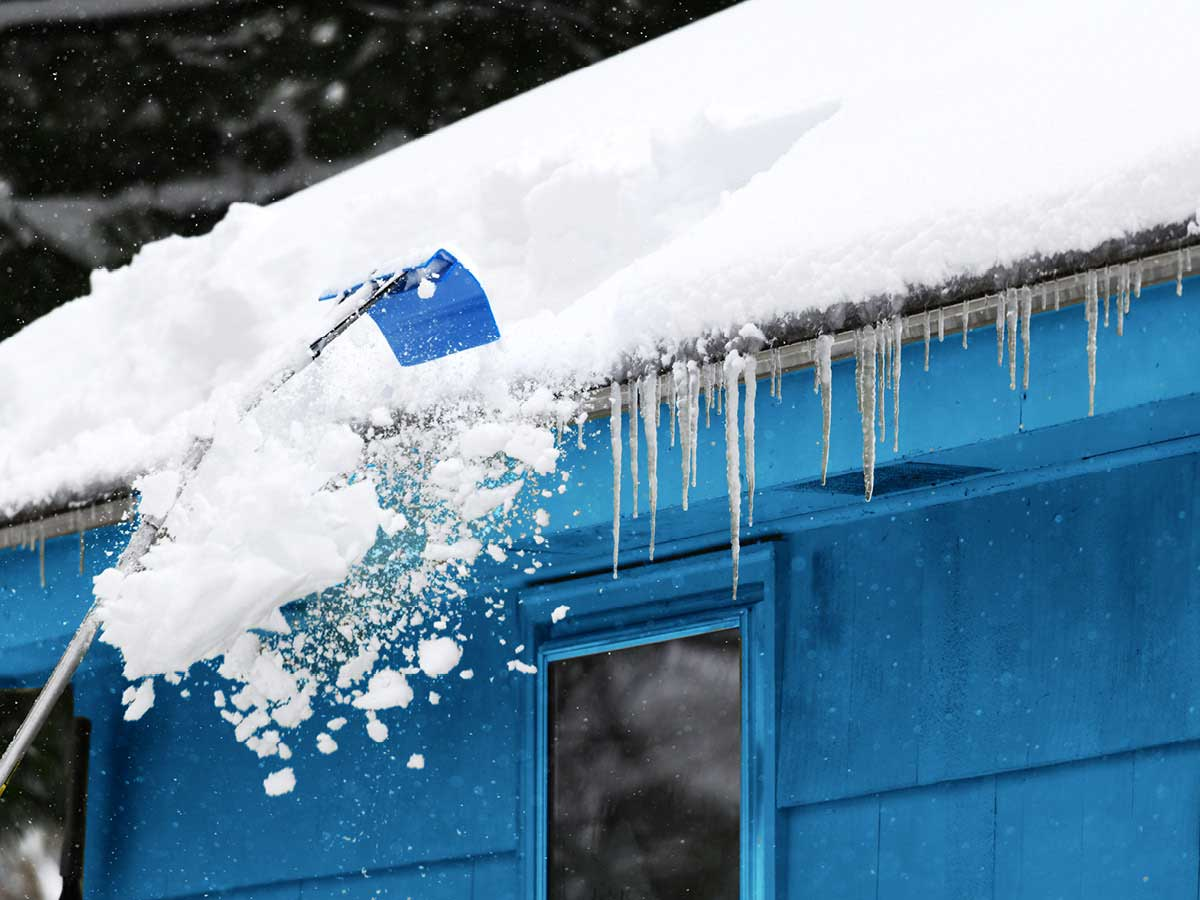 A snow-covered roof has icicles hanging from the eaves.